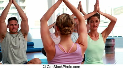 Happy yoga class sitting in lotus position