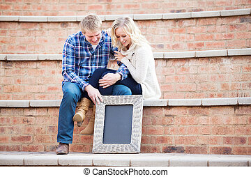 Happy young adult couple looking down at your text, focus on sign
