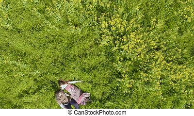 Happy young adult couple lying on rapeseed field.