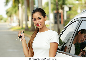 Happy young adult smiling and showing keys of new car
