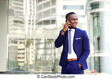 Happy young african american businessman with cell phone