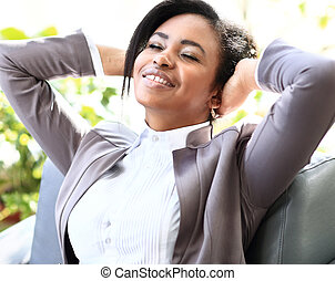happy young african american businesswoman relaxing in office