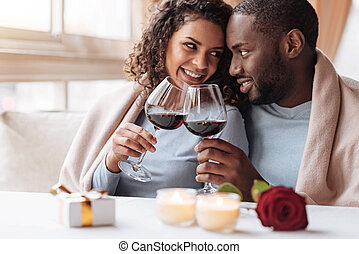 Happy young African American couple drinking wine in the restaurant