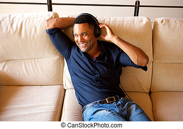 Happy young african american man looking away and smiling with head phones