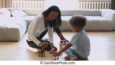 Happy young african american mother playing with little biracial kid.