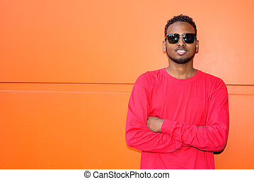 Happy young African bearded man smiling with arms crossed against orange wall