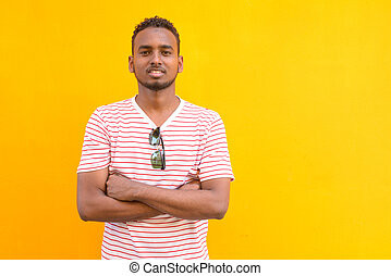 Happy young African bearded man smiling with arms crossed against yellow wall
