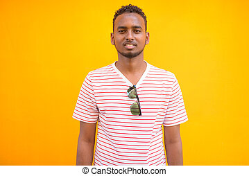 Happy young African bearded man with Afro hair against yellow wall