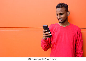 Happy young African bearded man with Afro hair using phone against orange wall