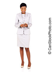 young african business woman texting on her smart phone