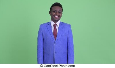 Happy young African businessman in suit smiling