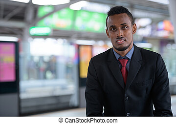 Happy young African businessman waiting at the train station