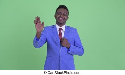 Happy young African businessman waving hand
