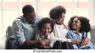 Happy young african ethnicity married couple cuddling smiling children.