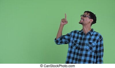 Happy young African hipster man pointing up and looking excited