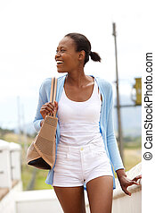 Happy young african lady walking outdoors