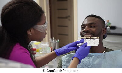 Happy young african man in a green shirt in the dentist's ...