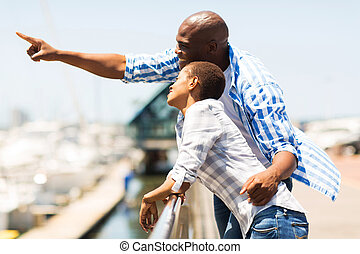 young african man pointing at the harbor with girlfriend