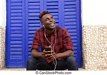 Happy young african man sitting outdoors with mobile phone and looking away