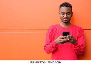 Happy young African man with Afro hair using phone against orange wall