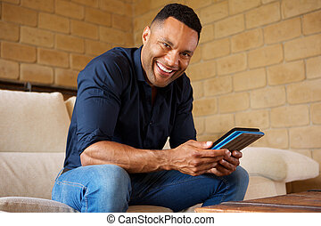 Happy young african man with digital tablet sitting in living room