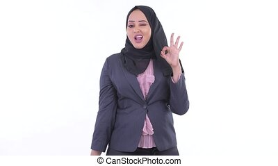 Happy young African Muslim businesswoman with ok sign -...