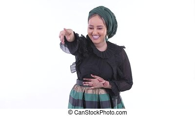 Happy young African Muslim woman laughing while pointing...