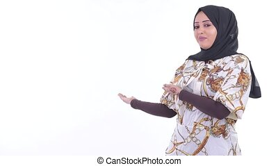 Happy young African Muslim woman talking while showing to...