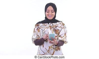 Happy young African Muslim woman using phone - Studio shot...