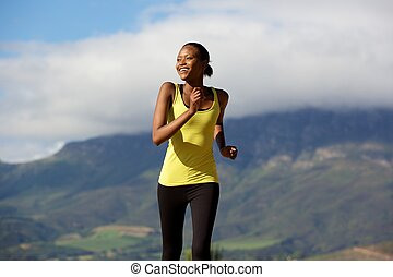 Happy young african woman doing running workout
