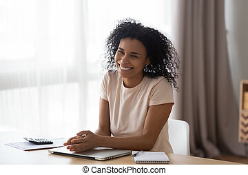 Happy young african woman laughing sitting at home office desk