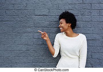 Happy young african woman pointing at copy space