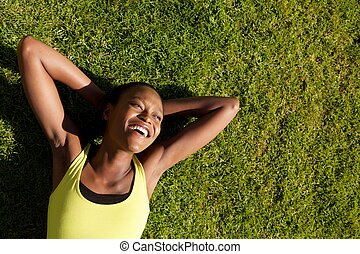 Happy young african woman resting on grass after workout