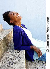 Happy young african woman sitting outdoors on steps