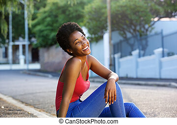 Happy young african woman sitting outdoors
