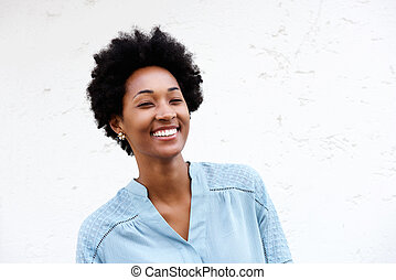 Happy young african woman standing against white wall