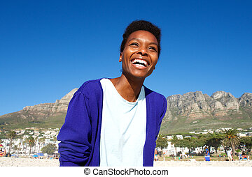 Happy young african woman standing outdoors on beach