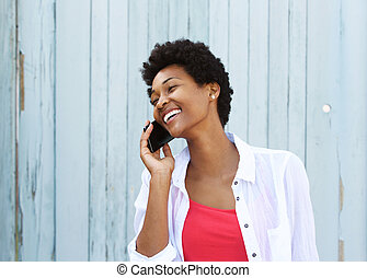 Happy young african woman talking on cell phone