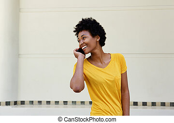 Happy young african woman talking on mobile phone