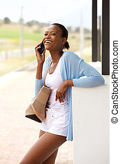 Happy young african woman with bag talking on mobile phone