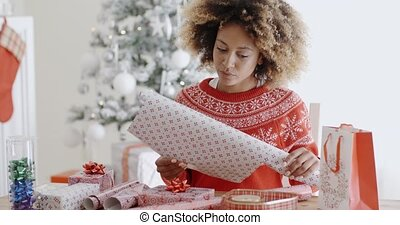 Happy young African woman wrapping presents at a table in...