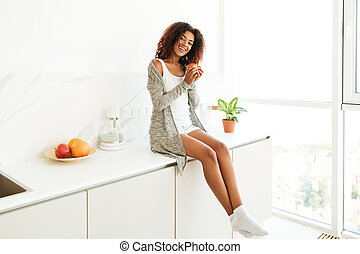Happy young afro american woman sitting on a kitchen table