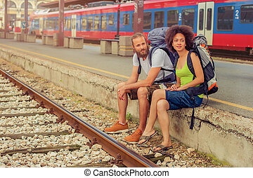 Happy young and beautiful couple of tourists sitting at the railway station