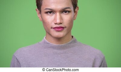 Happy young androgynous Asian man smiling