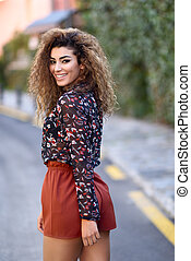 Happy young arabic woman with black curly hairstyle.