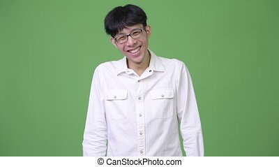 Happy young Asian businessman laughing