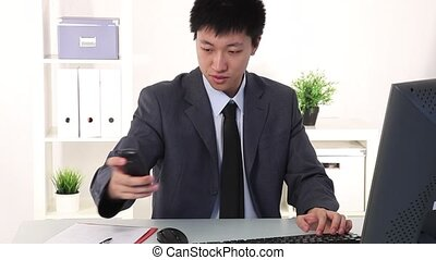 Happy young Asian businessman screa