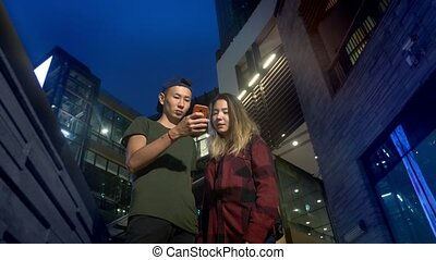 happy young asian couple boyfriend and girlfriend. use a smartphone while standing on a city street in the evening.