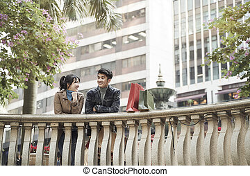 happy young asian couple chatting outdoors