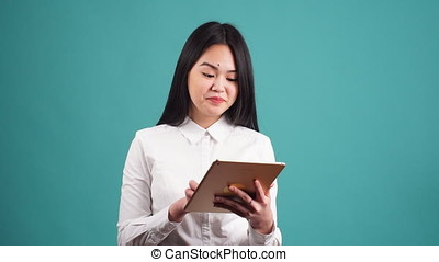 Happy Young Asian Girl Using Tablet Computer Isolated on a Blue Background.
